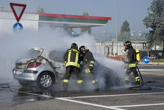 Firemen extinguishing a car fire Stock Photography