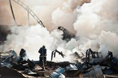 Firemen extinguishing fire Stock Image