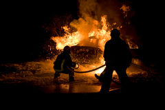 Firemen fighting a flaming car Royalty Free Stock Image