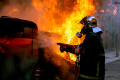 Firemen fighting a flaming car after an explosion Stock Image