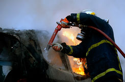 Firemen fighting a flaming car after an explosion Stock Images