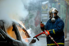 Firemen fighting a flaming car after an explosion Stock Photo