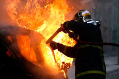 Firemen fighting a flaming car after an explosion Royalty Free Stock Image