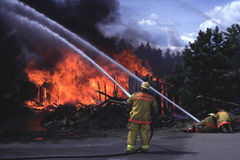 Firemen fighting house fire Stock Images