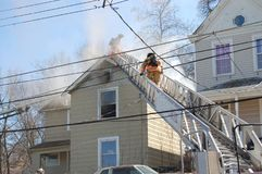 Firemen fighting house fire. Firemen fighting a roof fire on a quiet neighborhood street royalty free stock image