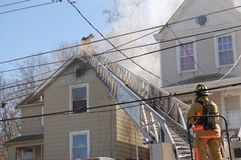 Firemen fighting house fire. Firemen fighting a roof fire on a quiet neighborhood street royalty free stock photo