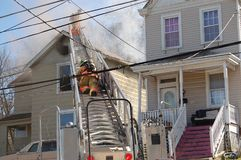 Firemen fighting house fire. Firemen fighting a roof fire on a quiet neighborhood street stock photos