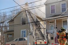 Firemen fighting house fire. Firemen fighting a roof fire on a quiet neighborhood street royalty free stock photography