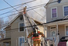 Firemen fighting house fire. Firemen fighting a roof fire on a quiet neighborhood street royalty free stock images