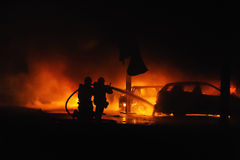 Firemen fighting vehicle fire at night. Firemen fighting passenger vehicle fire at night Royalty Free Stock Photo