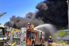 Firemen on a Fire truck. Firemen fight a fire at a burning building Stock Images