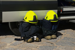 Firemen gear. Firemen helmet, suite and boots next to fire truck Royalty Free Stock Image
