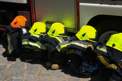 Firemen gear. Firemen helmets, suites and boots aligned next to fire truck Stock Photography