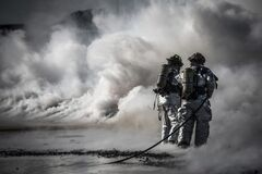 Firemen with hoses in smoke