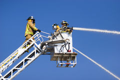 Firemen on ladder. Three firemen on lift ladder spraying powerful streams of water, blue sky background royalty free stock photo