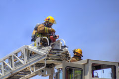 Firemen on a ladder truck. Firemen mount a nozzle on a ladder truck aerial Royalty Free Stock Photos