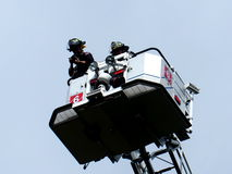 Firemen In Ladder Truck Stock Photo
