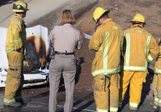 Firemen and Police Officer. Four Firemen and Female Police Officer at Car Fire Royalty Free Stock Photos