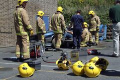 Firemen practice cutting an injured driver out of a wrecked car stock image