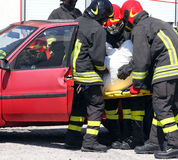 Firemen pull the injured from the car after the car accident Royalty Free Stock Photos