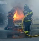 Firemen putting out a car on fire Stock Image
