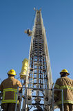 Firemen raise a ladder. Two firemen raise a ladder in preparation to fight a fire Stock Images