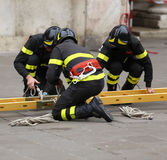 Firemen during rescue operations with a wooden ladder Stock Photography