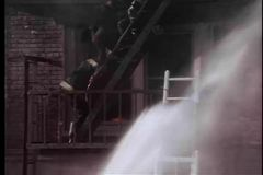 Firemen rescuing victim on fire escape of burning building stock footage