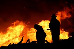 Firemen Silhouette. Silhouette of two firemen fighting a raging fire with huge flames of burning scrap timber Stock Photo