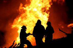 Firemen Silhouette. Silhouette of three firemen fighting a huge fire of burning timber Stock Photography