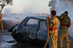 Firemen at site of car crash. Fireman extinguishing a fire on the remains of a vehicle involved in a serious automobile accident Stock Image