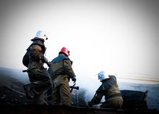 Firemen In a special form on the roof of a burning house Stock Images