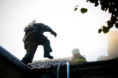 Firemen In a special form on the roof of a burning house Royalty Free Stock Photo