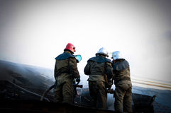 Firemen In a special form on the roof of a burning house Royalty Free Stock Image