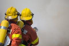 2 firemen spraying water in fire and smoke. 2 firemen spraying water in fire fighting with fire and dark smoke background Royalty Free Stock Photos