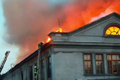 Firefighters on the roof of a house that is on fire stock photos