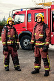 Firemen standing next to fire truck. Portrait of two firemen standing next to fire truck at base Stock Photography