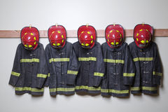 Firemen suits and helmets. Hanging inside a room Royalty Free Stock Photography