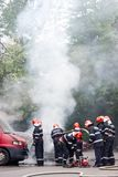 Firemen team extinguishing a car on fire. Bucharest, Romania - May 07, 2018: Cars on fire blow up on the streets of Bucharest Royalty Free Stock Photos