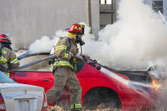 Firemen training on a burning car Stock Photos