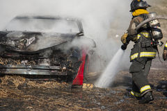 Firemen training on a burning car Stock Image