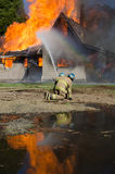 Firemen Training. A seasoned fireman shows a new recruit how to handle a fire hose at a burn to learn session stock images