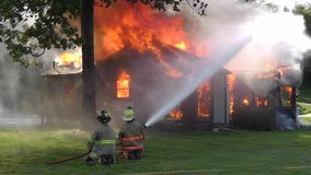 Firemen trying to control the flames of a house fire. stock footage
