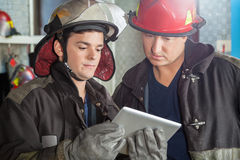 Firemen Using Digital Tablet At Fire Station Stock Photos