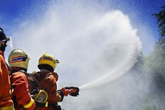 Firefighter during training. Firemen using extinguisher and water for fight fire during firefight training. All fighter wearing fire suit for safety under danger Royalty Free Stock Photography