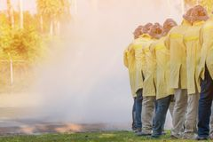 Firemen using extinguisher and water from hose for fire fighting. At firefight training of insurance group. Firefighter wearing a fire suit for safety under the stock photography