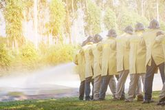 Firemen using extinguisher and water from hose for fire fighting. At firefight training of insurance group. Firefighter wearing a fire suit for safety under the royalty free stock images