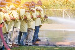 Firemen using extinguisher and water from hose for fire fighting. At firefight training of insurance group. Firefighter wearing a fire suit for safety under the royalty free stock image