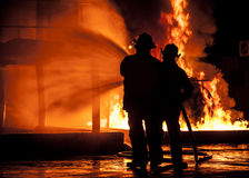 Firemen using water hose on raging fire Stock Image