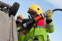 Firemen With Power Wedge At Car Crash Stock Photos